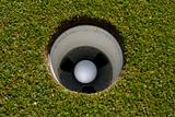 Golf ball at rest in hole