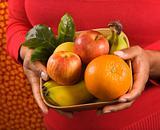 Hands holding fruit basket.