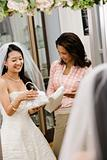 Woman helping bride with handbags.