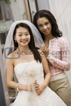 Bride and friend admiring dress.