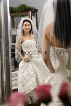 Bride admiring dress.