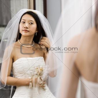 Bride looking at mirror.