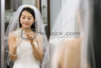 Bride looking at bouquet.