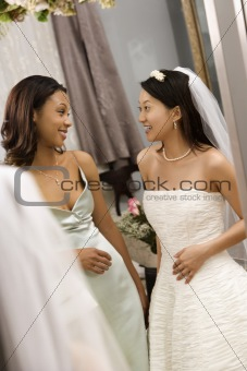 Bride and bridesmaid talking.