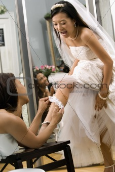 Bridesmaid placing garter.