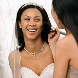 Bridesmaid applying makeup to bride.