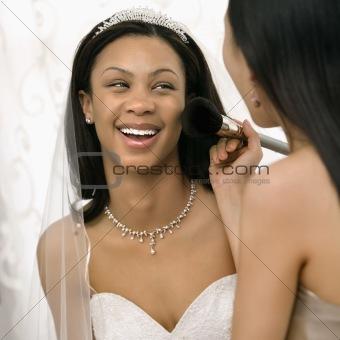 Bridesmaid applying makeup to bride.