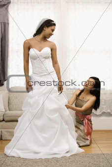Bridesmaid adjusting bride's dress.
