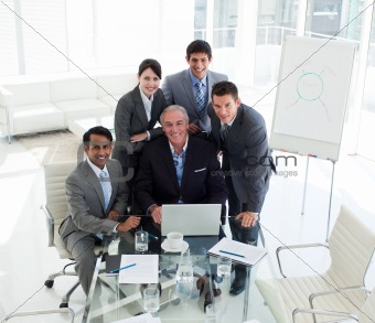 Senior businessman working with his team at a computer