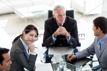 Attractive businesswoman sitting at a conference table with her