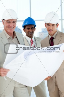Smiling architects with hardhat looking at blueprints