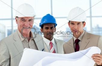 Smiling architects studying blueprints