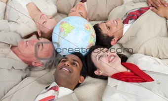 Smiling business people lying around a globe