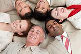 Business team lying on the floor with heads together
