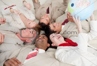Business team lying on the floor playing with a terrestrial glob