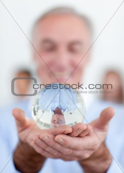 Senior businessman holding a crystal ball