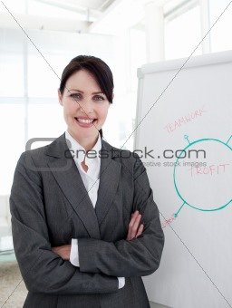 Smiling businesswoman with folded arms at a presentation