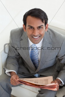 Businessman reading a newspaper and sitting in a waiting room