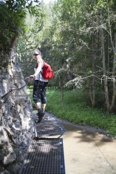 tourist girl walking through the canyon on metal pads