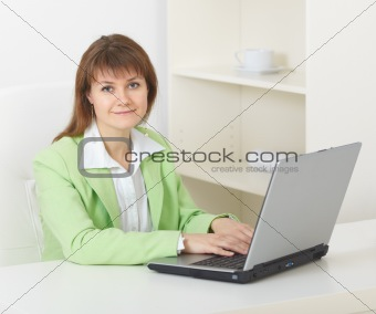 Young woman with laptop sits at table at office