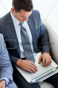 Attractive businessman using a laptop while waiting for a job in