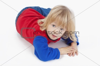 boy with long blond hair lying down, looking at camera