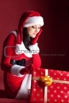 beautiful brunette in Christmas dress opens gift.