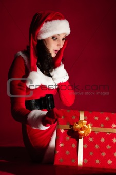 beautiful brunette in Christmas dress opens gift