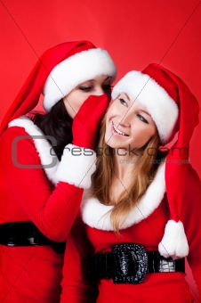 Two happy young Santa girl talking