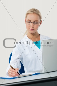 Beautiful female doctor working on her laptop