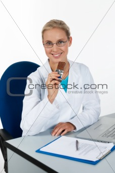Beautiful female doctor eating chocolate while working in her of