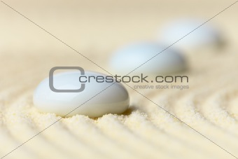 Three white drops on surface of yellow sand
