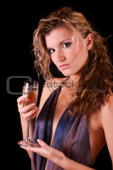 Beautiful woman posing with glass of champagne on black background