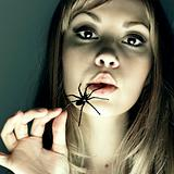 Young woman with spider in a mouth