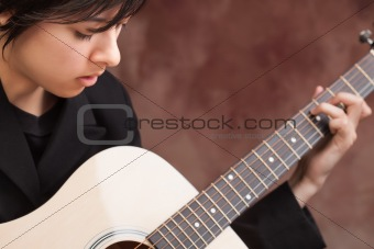 Attractive Ethnic Girl Enjoys Playing Her Guitar.