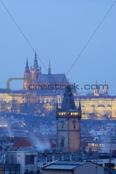 prague - old town city hall tower and hradcany castle at dusk