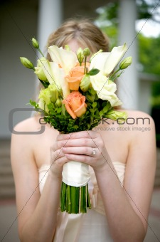 Bride Holding Bouquet Over Face