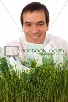 Businessman with green banknotes in grass