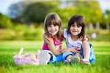 Two young smiling girls hugging in the grass
