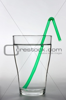 a full water glass with a green drinking straw