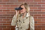 women in a trenchcoat with binoculars