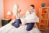 Young Couple Kneeling on Bed Having a Pillow Fight