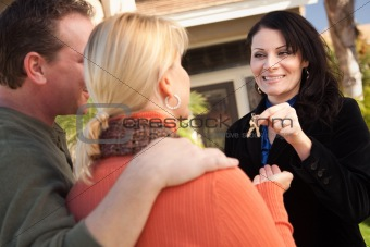 Attractive Hispanic Female Real Estate Agent Handing Over New House Keys to Happy Couple.