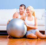 Couple Sitting on Floor With Silver Exercise Ball