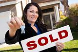 Happy Attractive Hispanic Woman Holding Keys and Sold Sign In Front of House.