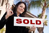 Happy Attractive Hispanic Woman Holding Sold Sign and In Front of House.