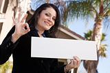 Happy Attractive Hispanic Woman Holding Blank Sign in Front of House.