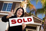 Happy Attractive Hispanic Woman with Thumbs Up Holding Sold Sign In Front of House.
