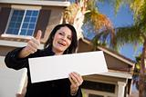 Happy Attractive Hispanic Woman with Thumbs Up Holding Blank Sign in Front of House.