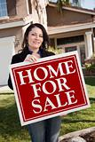 Happy Attractive Hispanic Woman Holding Home For Sale Real Estate Sign In Front of House.